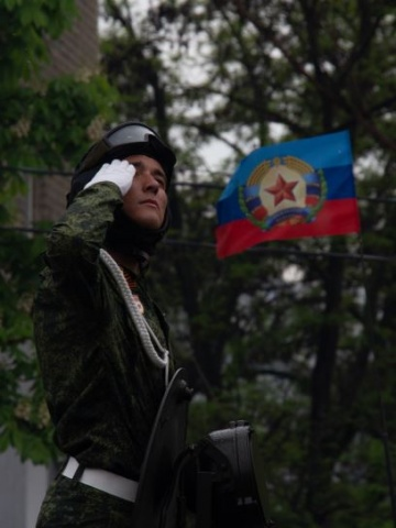 Soldier in front of the flag of the People's Republik of Lugansk (LNR)