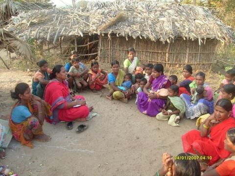 Women gathering in a makeshift Adivasi village
